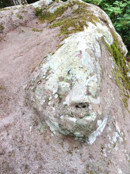 """""""wajah"""" penjaga huta/kampung di pahat pada batu."""